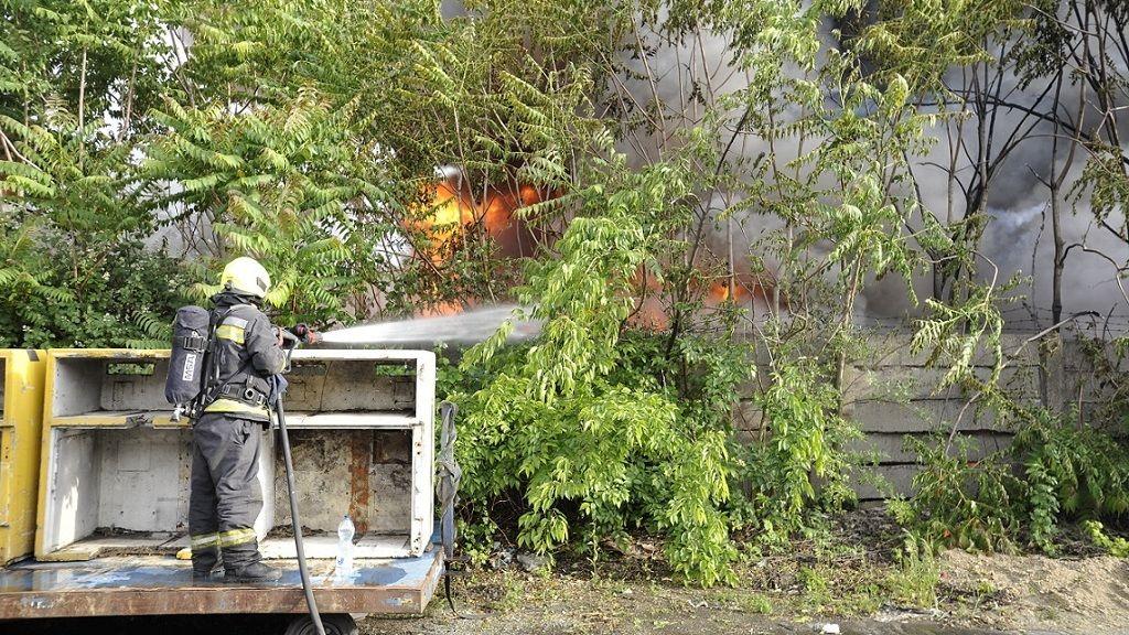 Tűzoltó Kőbányán, a Sírkert úton, egy ipari területen, ahol bontásra váró hűtőszekrények és egyéb fémhulladékok kaptak lángra 2020. június 5-én. - Fotó: MTI/Mihádák Zoltán