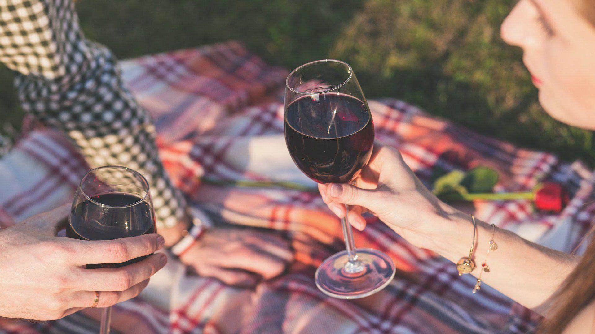 Egy férfi és egy nő bort iszik a szabadban