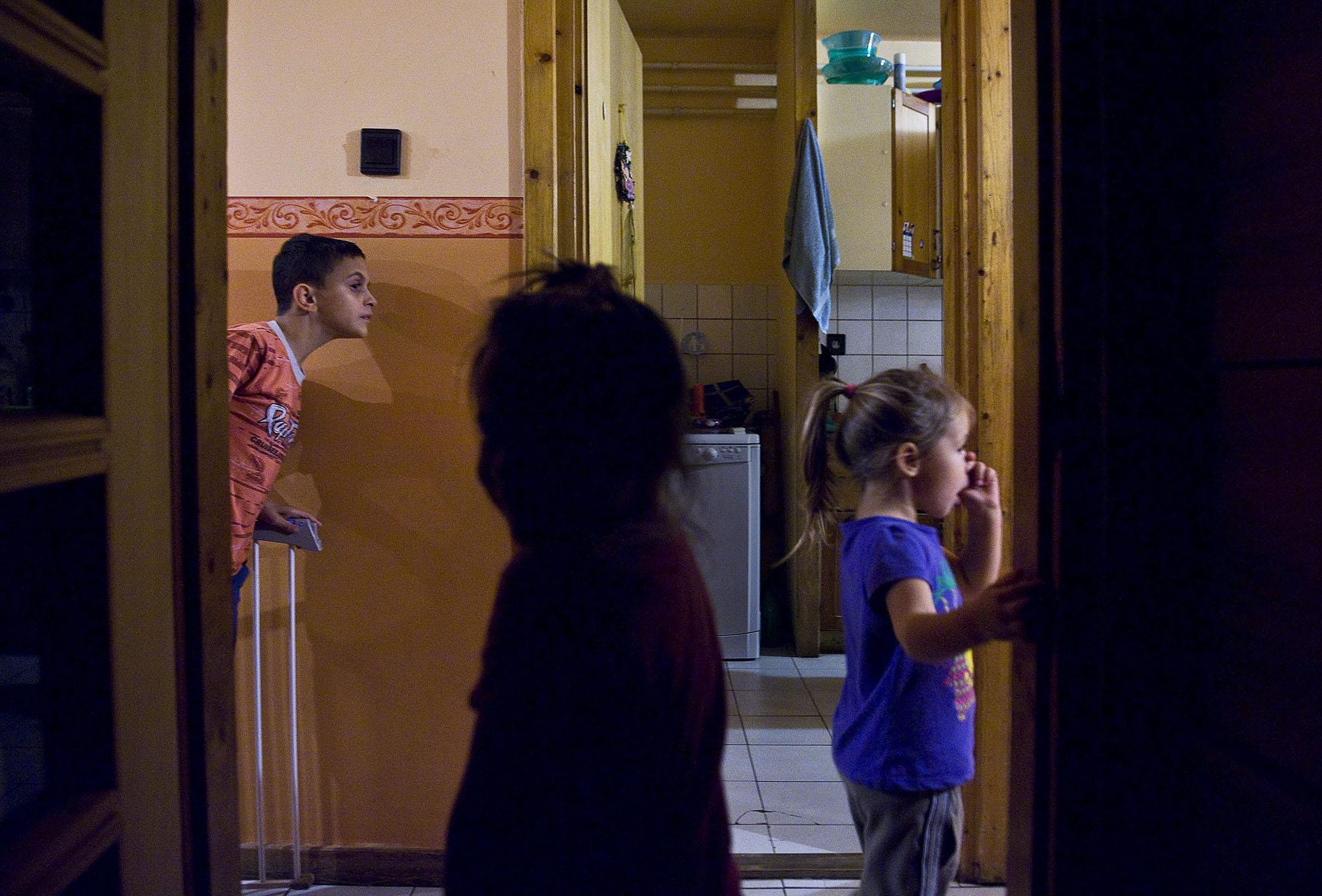 Gyerekek néznek be a folyosóról a konyhába vacsora előtt az SOS Gyermekfalu Magyarországi Alapítványának kecskeméti gyermekfalujában (fotó: MTI/Ujvári Sándor)