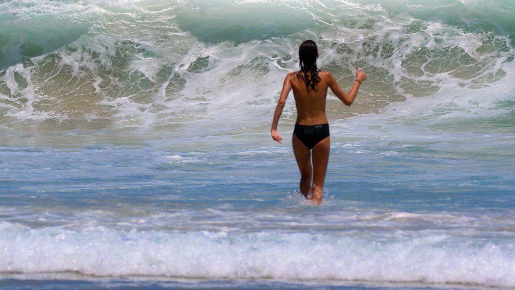 Félmeztelen strandoló a tengerben