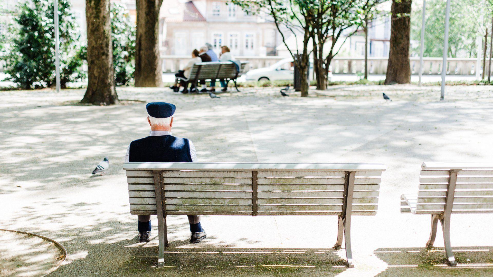 Idős férfi ül magányosan egy padon