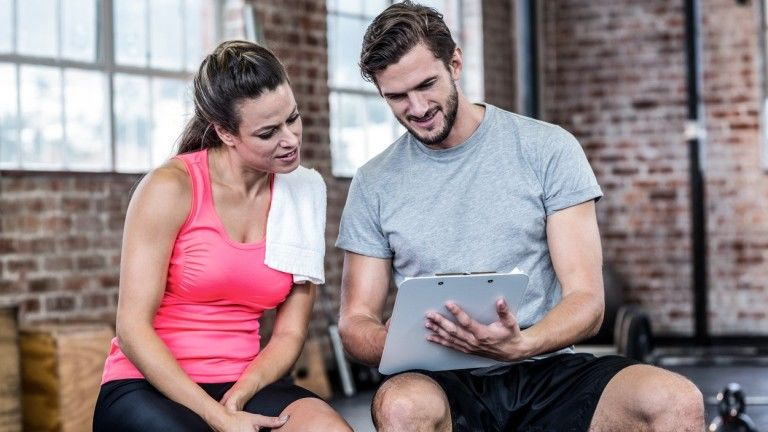 Fit woman discussing with personal trainer in crossfit gym