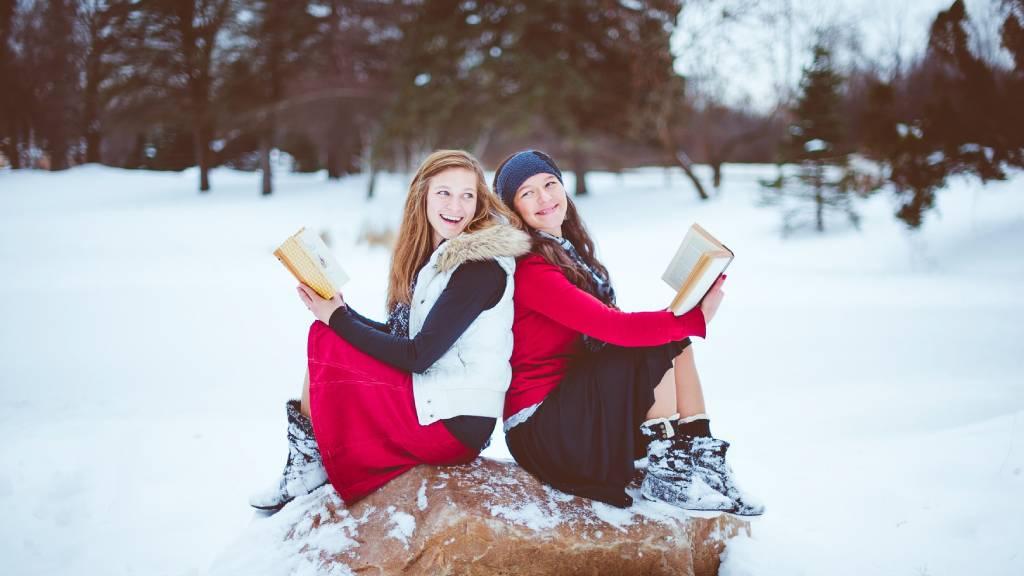 két vidám lány könyvvel a kezében hóban