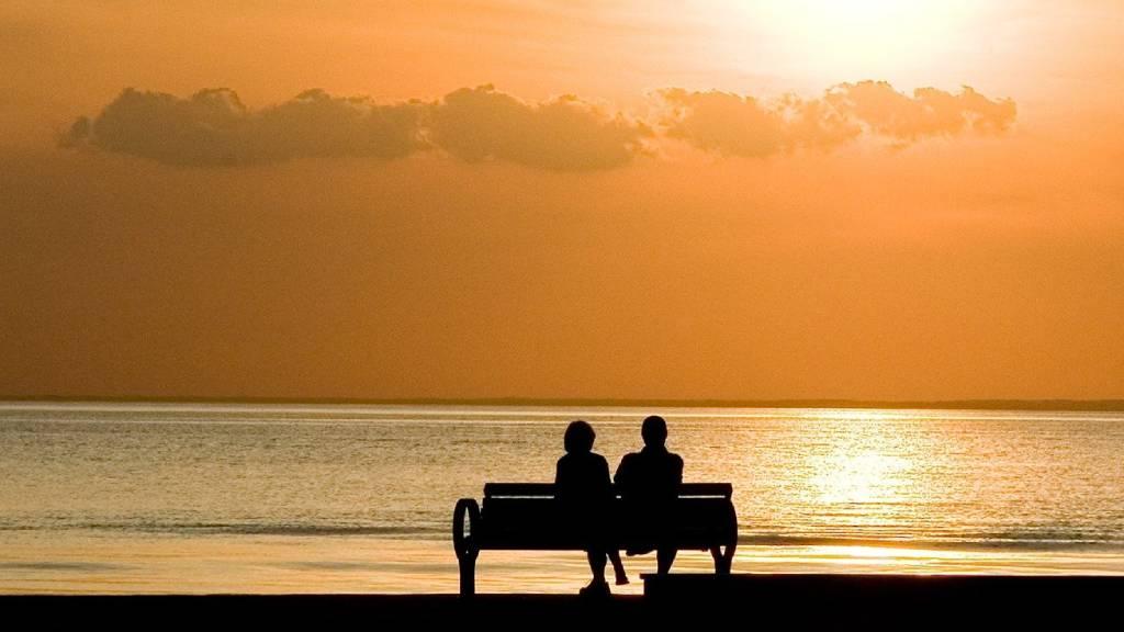 szerelmespár naplementében ül egy padon