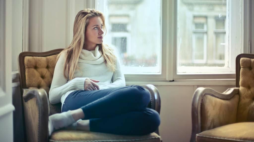 nő lakásban fotelben ül