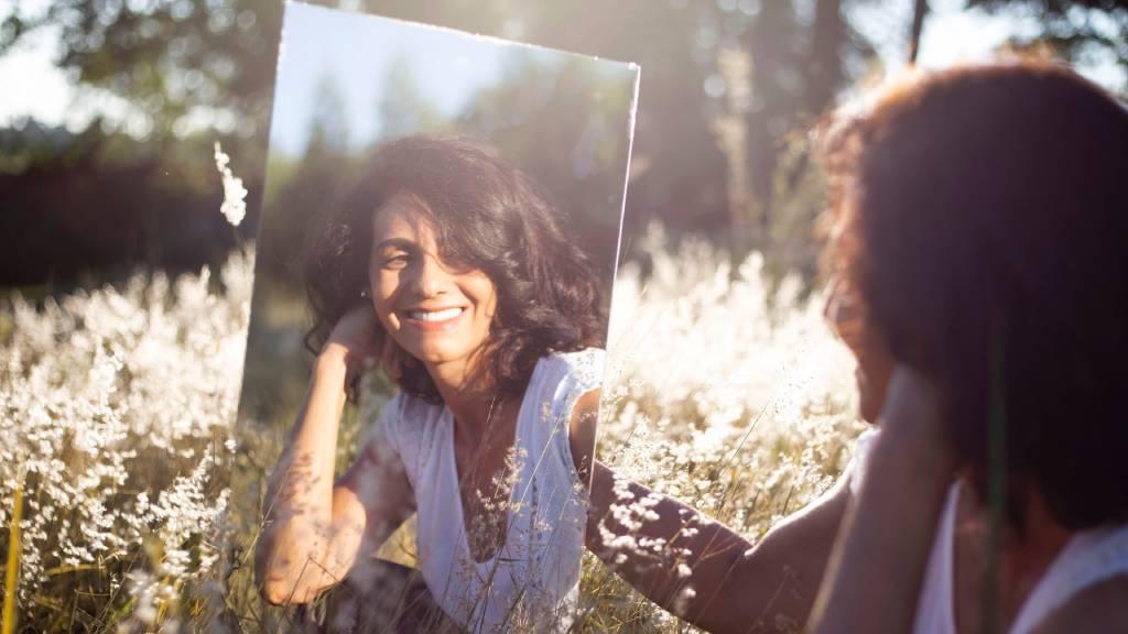 vidám nő nézi magát a tükörben