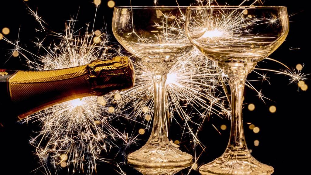 pezsgőspoharak és pezsgő tűzijátékkal
