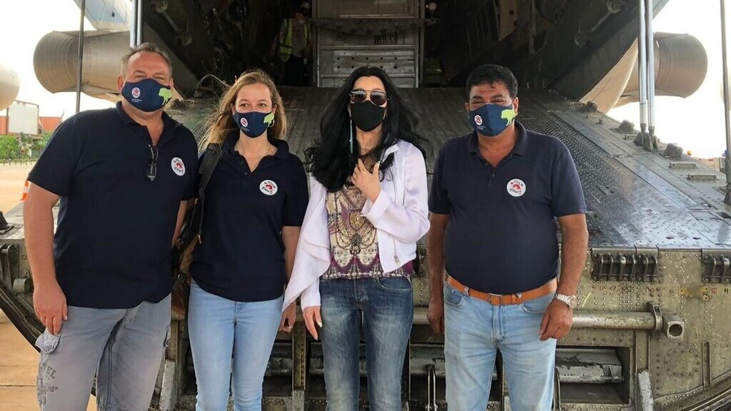 Cher (j2) és a brit Négy Mancs állatvédőszervezet munkatársai a szállítógép előtt (Fotó: 4 Paws FB)