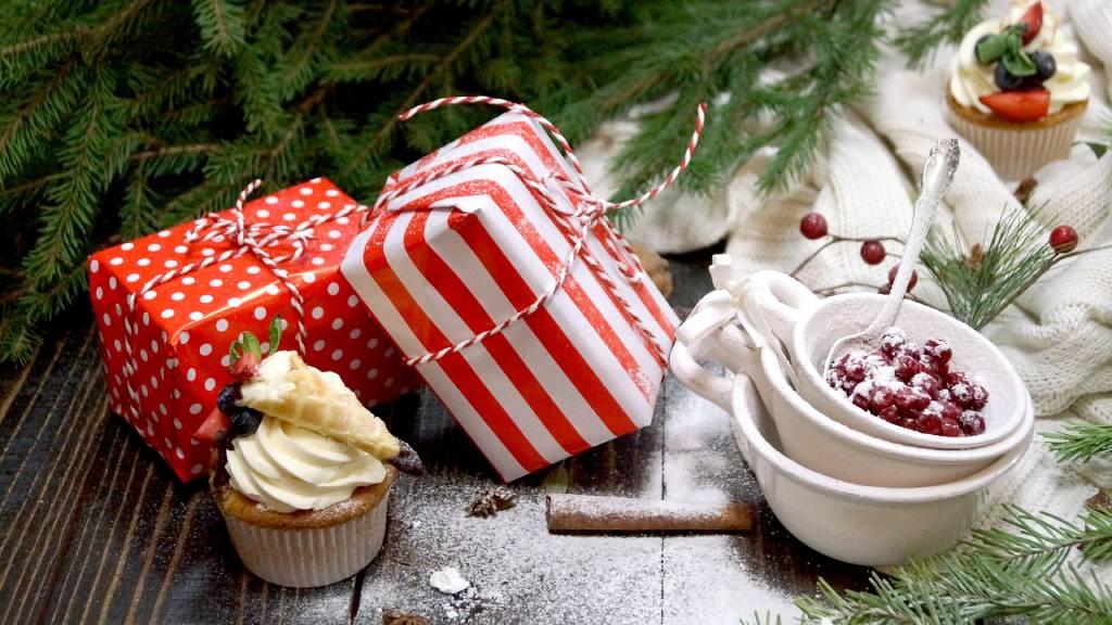 piros csomagok fenyőfa alatt édeségekkel