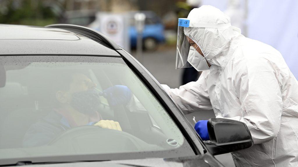 Mintát vesznek egy autóval érkező pácienstől a koronavírus-gyanús esetek szűrésére felállított mobil mintavételező állomáson.