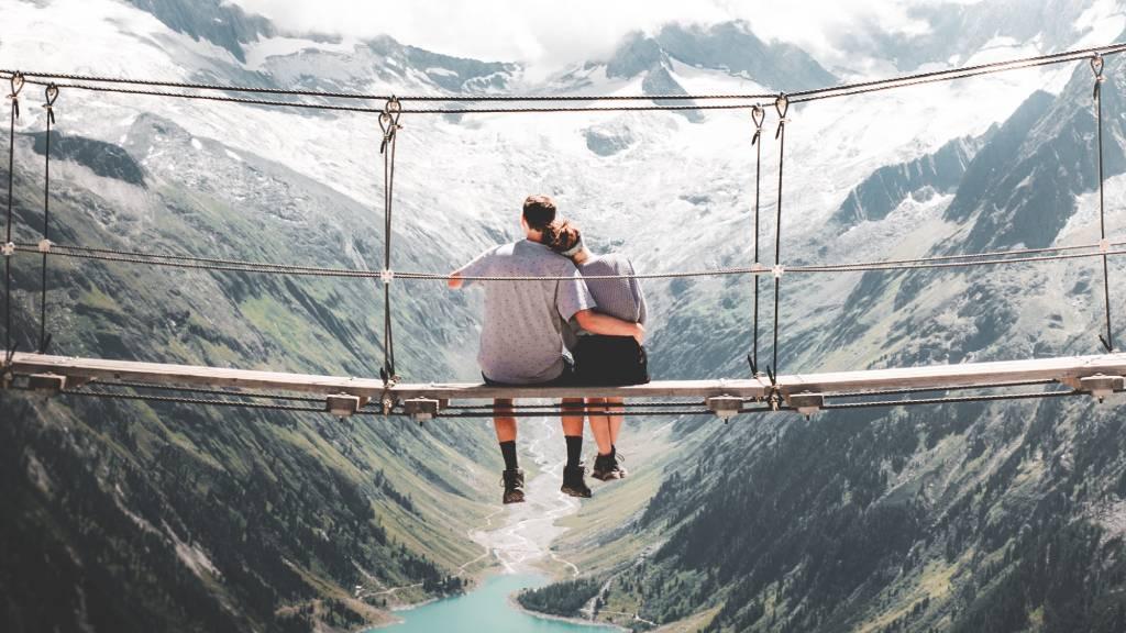 szerelmespár ül egy magas hegyi hídon