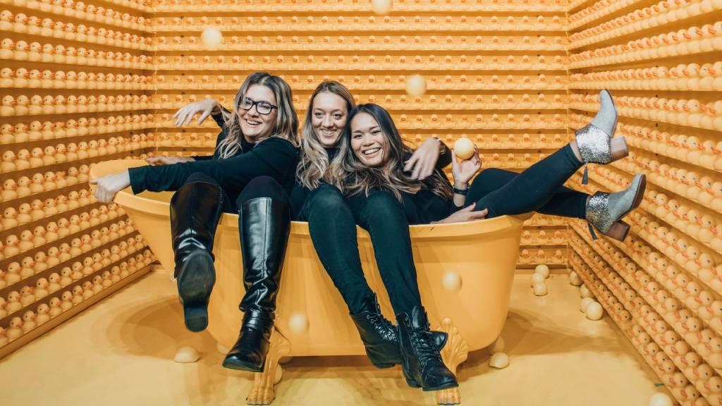 három boldog nő viccesen egy sárga kádban