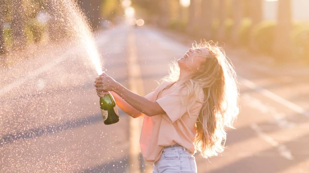 boldog nő pezsgőt locsol
