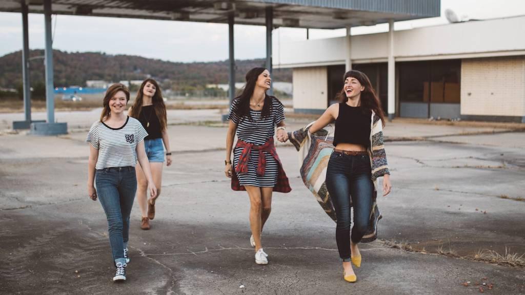 négy lány vidáman megy elhagyatott benzikútnál