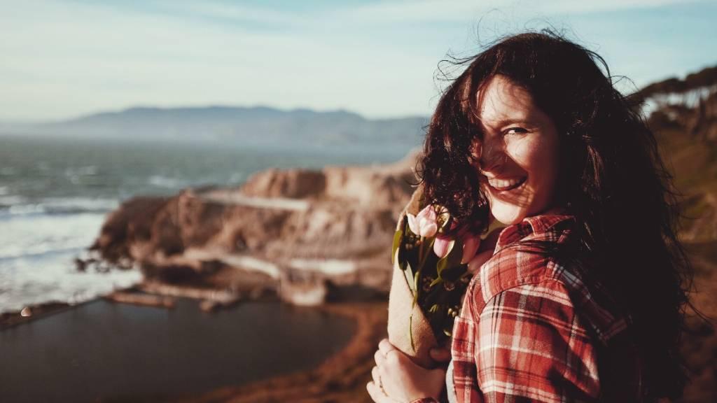 boldog nő a tengerparton áll virágcsokorral