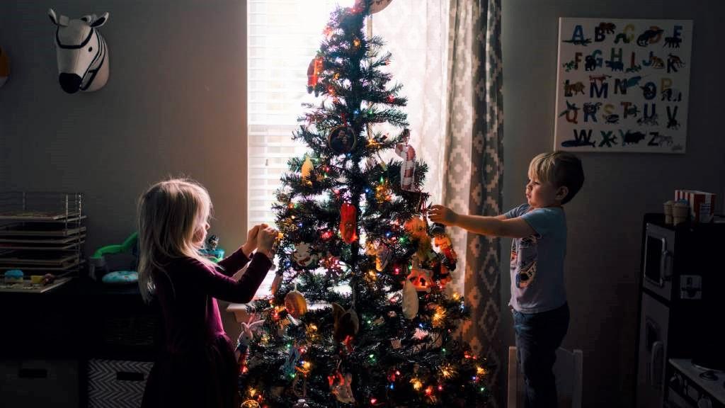 gyerekek karácsonyfát díszítenek