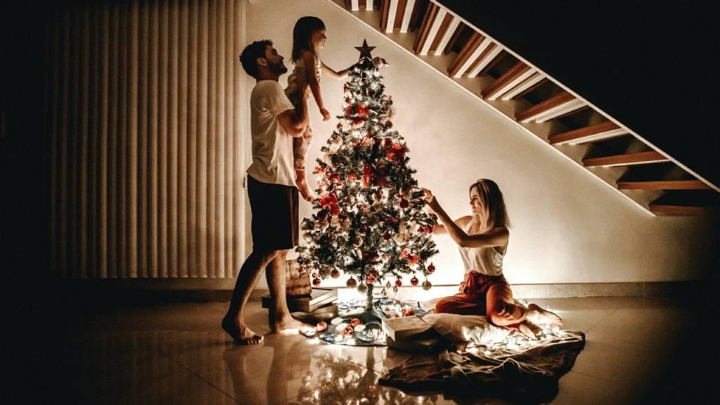 család karácsonyfát díszít