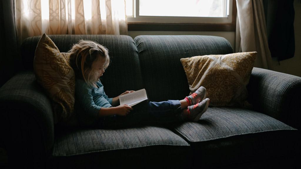 kislány olvas a kanapén