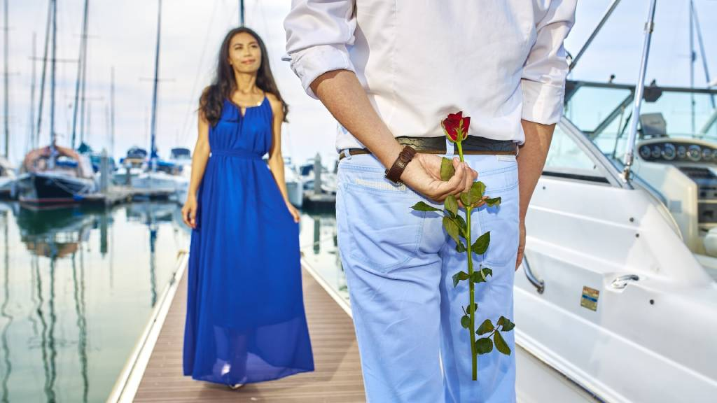 kék ruhás nő vitorlások közt rózsás férfival randizik