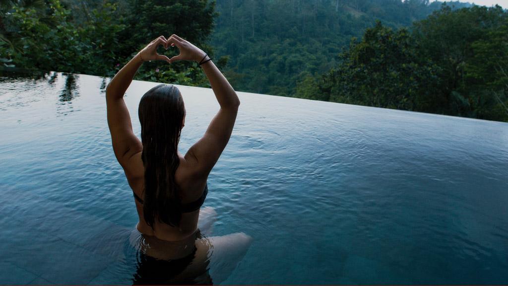 nő meditál és szívet mutat egy medencében