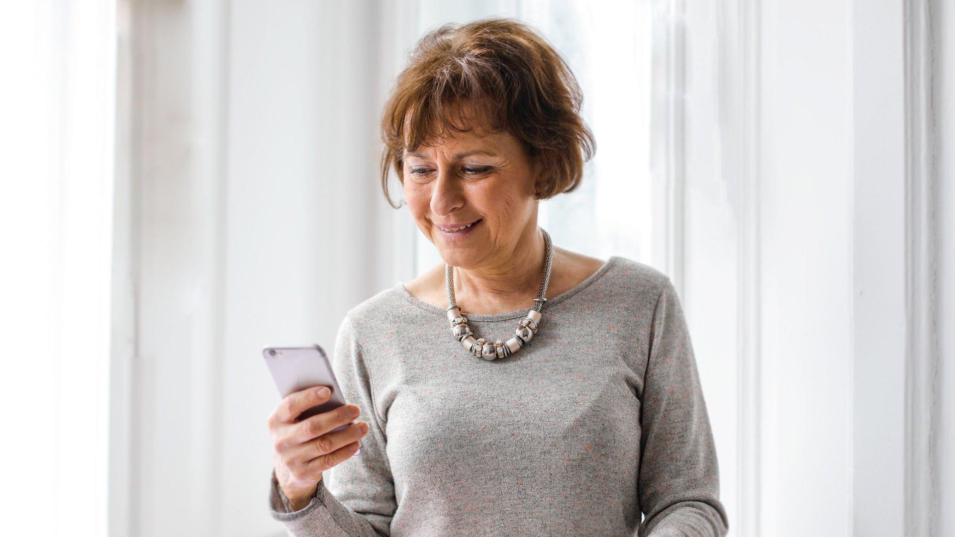 Középkorú nő telefonnal a kezében