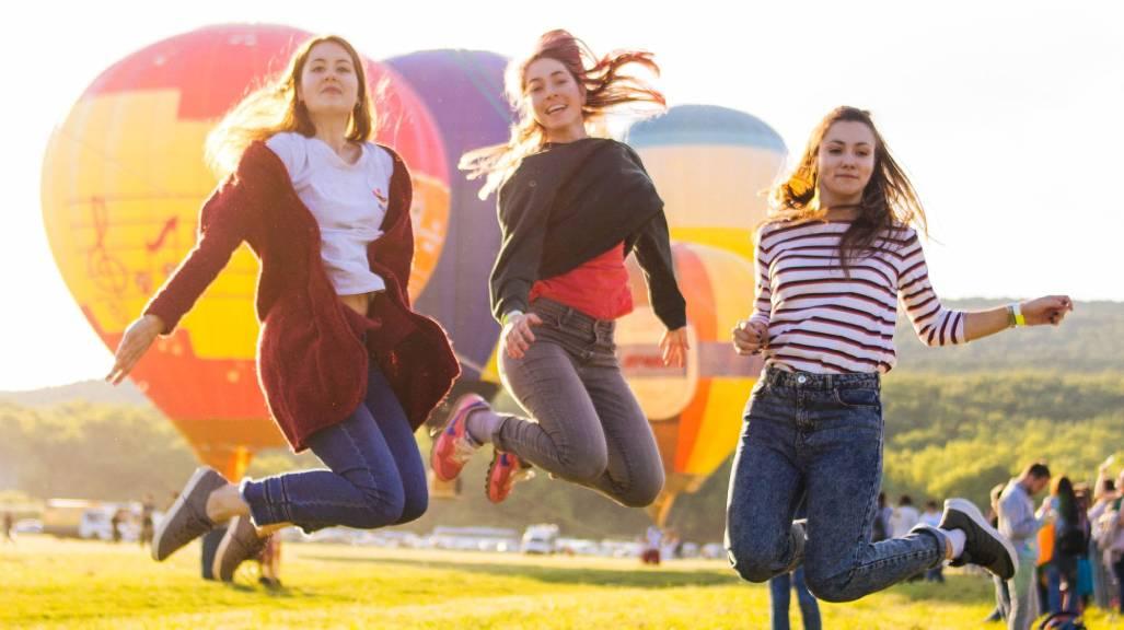 boldog nők ugranak színes hőlégballonok előtt
