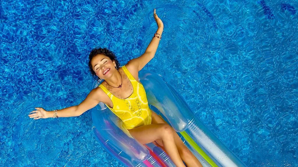 citromsárga fürdőruhás boldog nő medencében lebeg