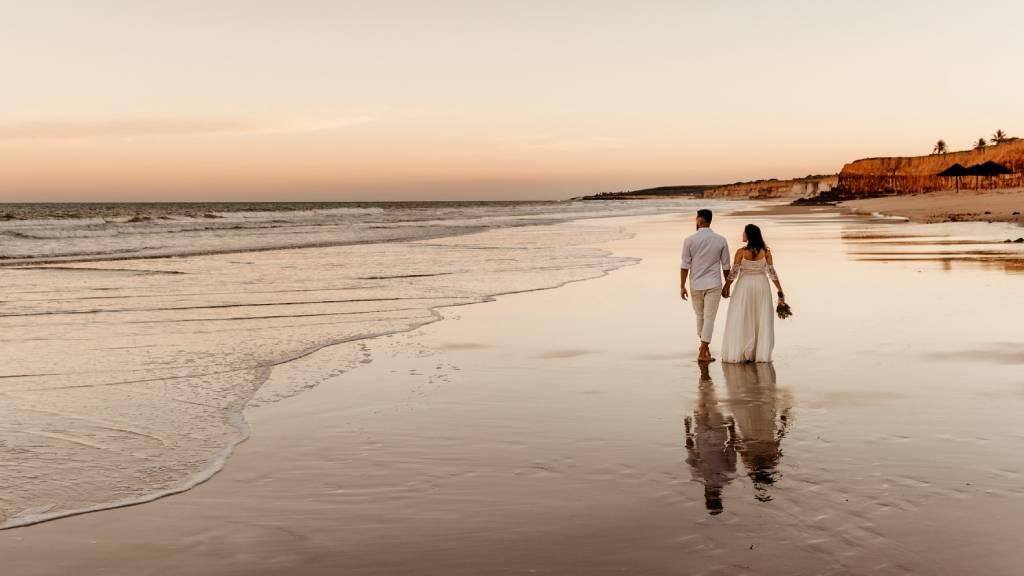 tengerparton sétáló esküvőiruhás pár