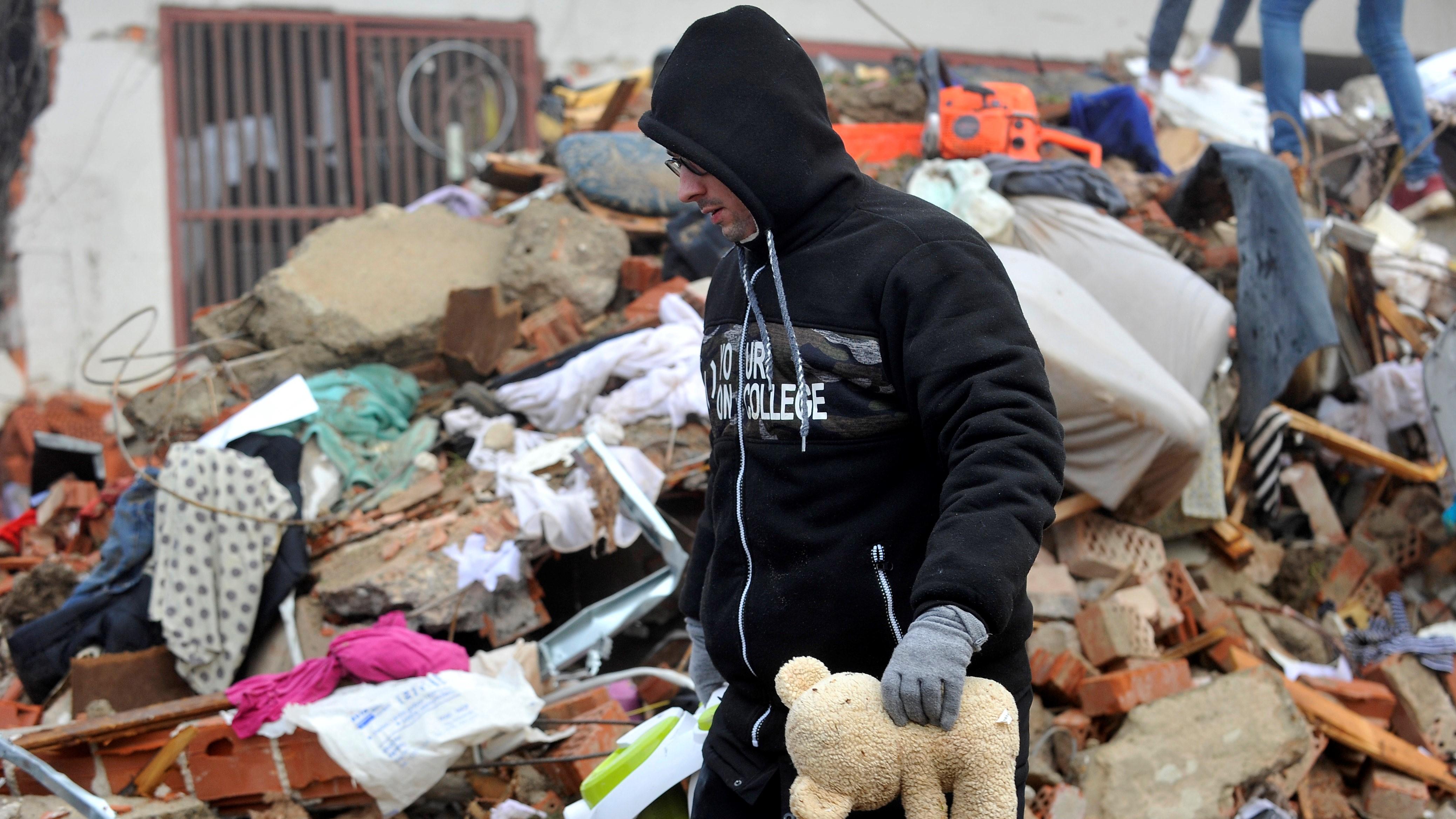 Összedőlt ház romjai között kutatnak az emberek a horvátországi Majske Poljane faluban 2020. december 30-án, egy nappal azután, hogy 6,3-as erősségű földrengés rázta meg az ország középső részét.