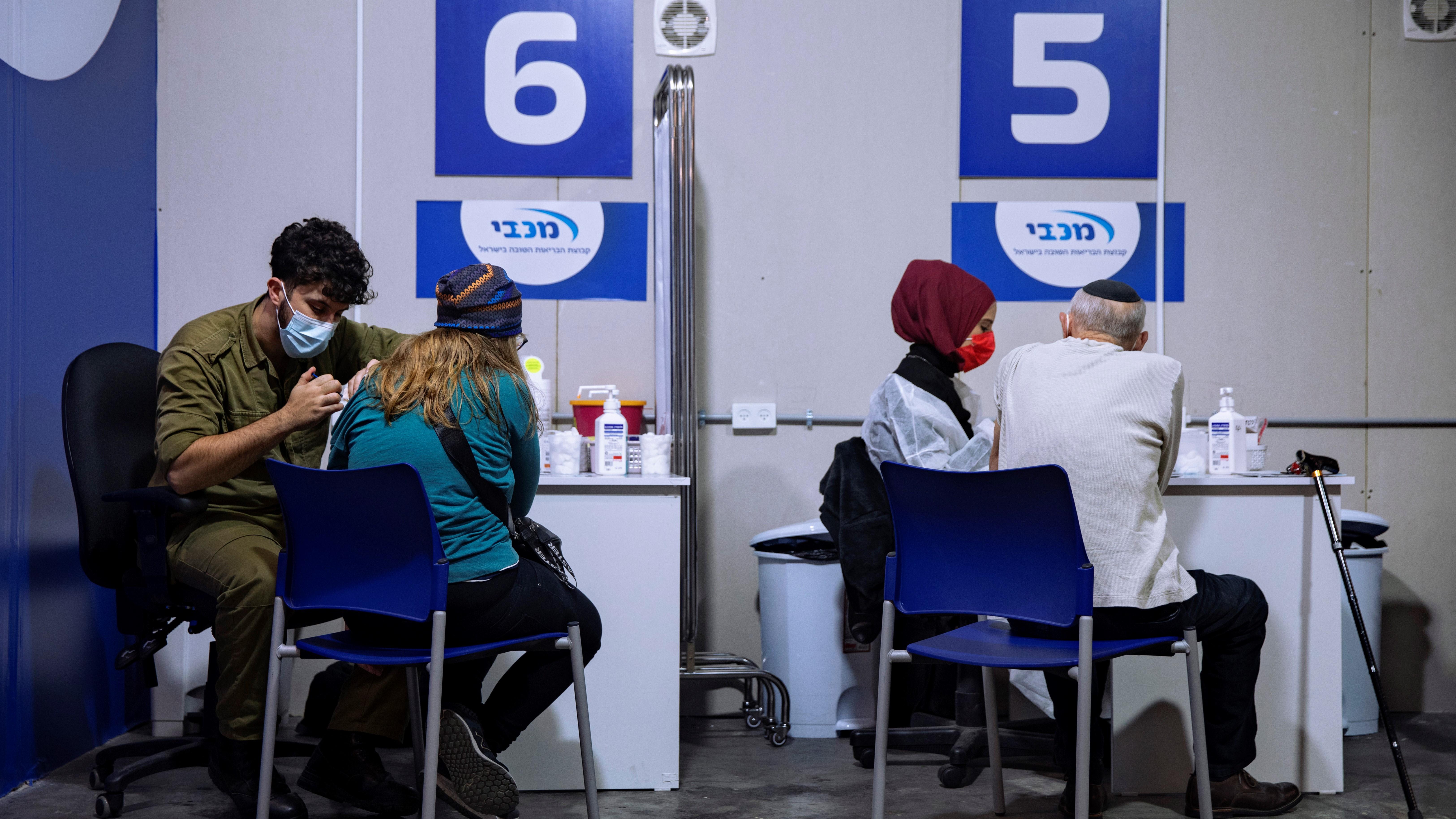 Izraelieket oltanak a Pfizer-BioNTech cégek koronavírus elleni vakcinájával egy bevásárlóközpont parkolójában, Givatayimban 2021. január 20-án.