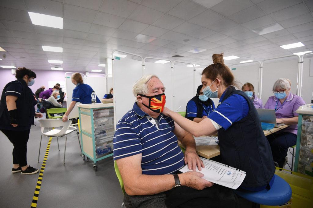 Koronavírus elleni oltóanyagot adnak be egy férfinak az angliai Hertfordshire megyei Stevenage város konferenciaközpontjában létesített oltóközpontban 2021. január 11-én.