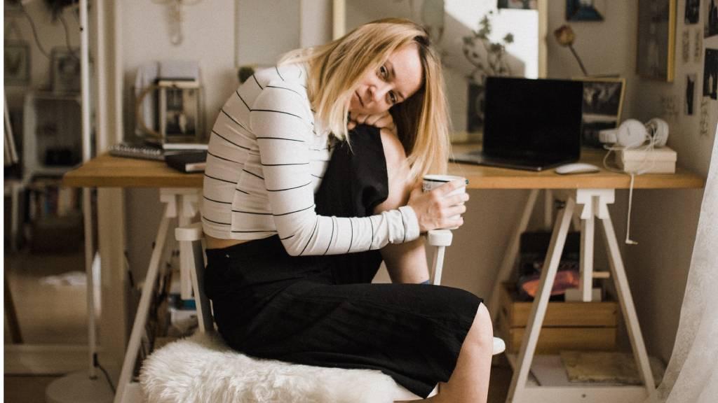 nő mélázva ül tükör előtt pohárral a kézben