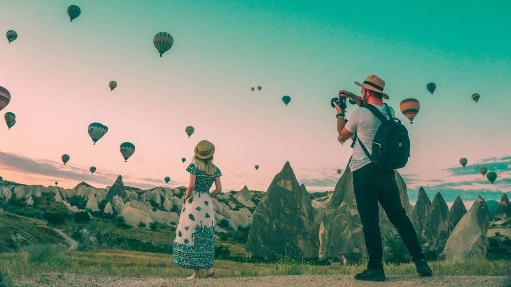 hőlégballonok között férfi fotózza a nőt