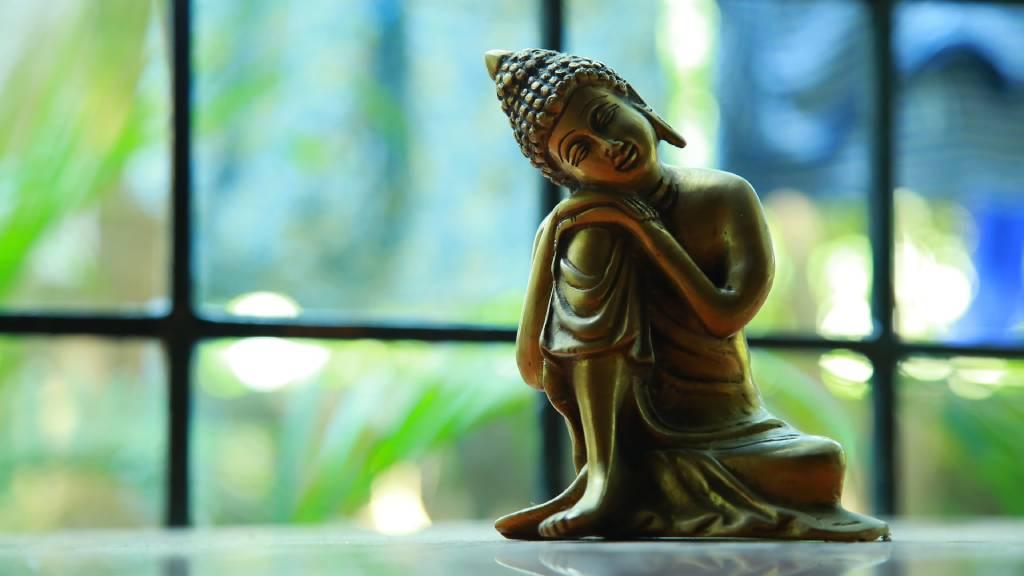 buddha szobor egy ablak előtt