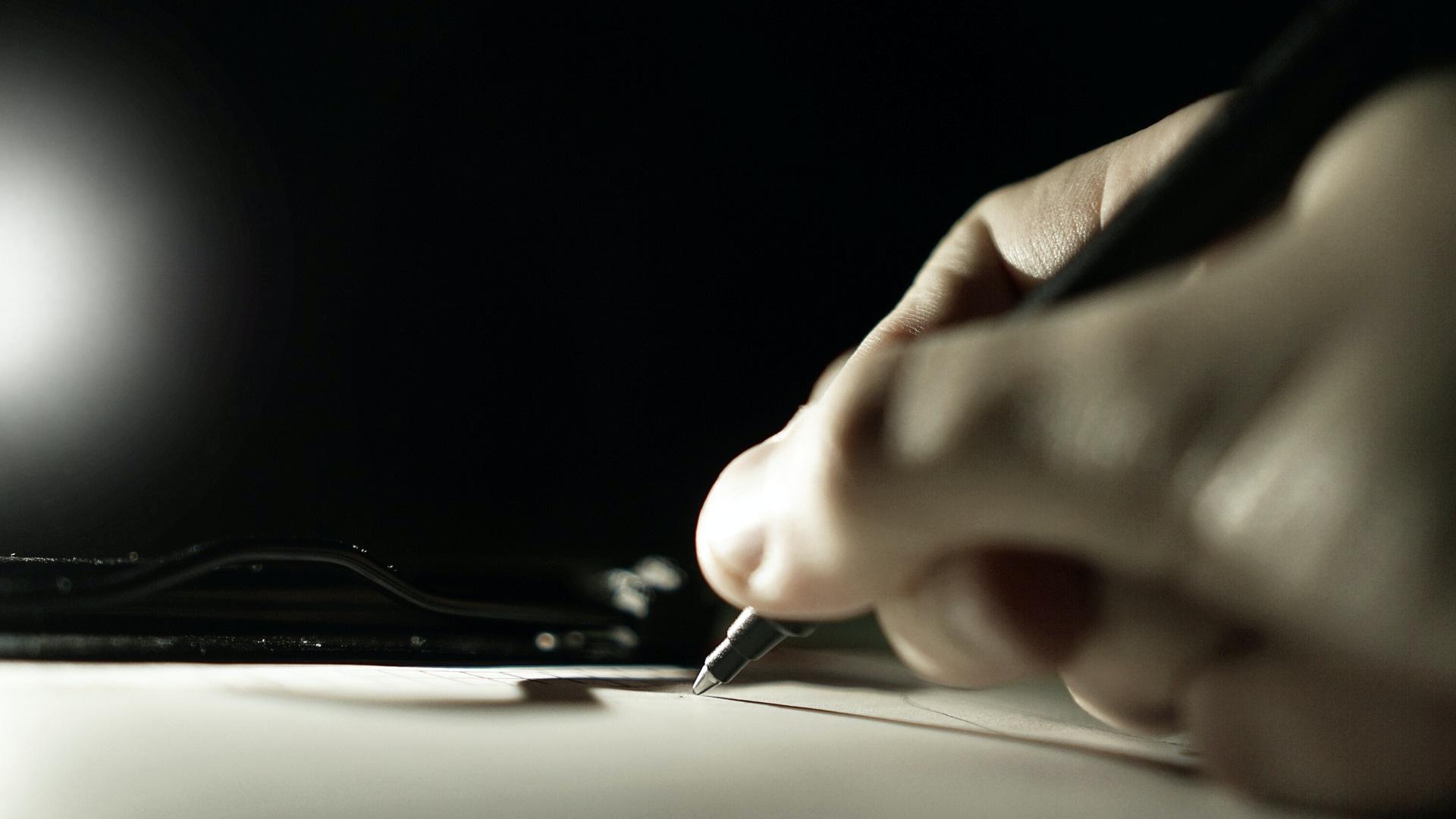 Tollal ír egy papírra