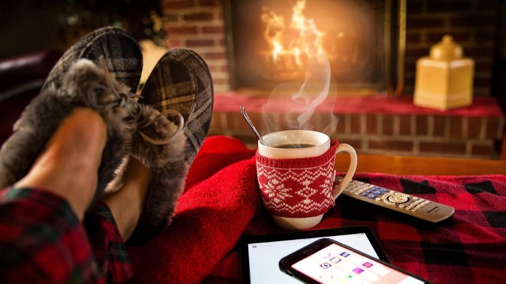 pihenés, lábak forró itallal téli kandalló előtt