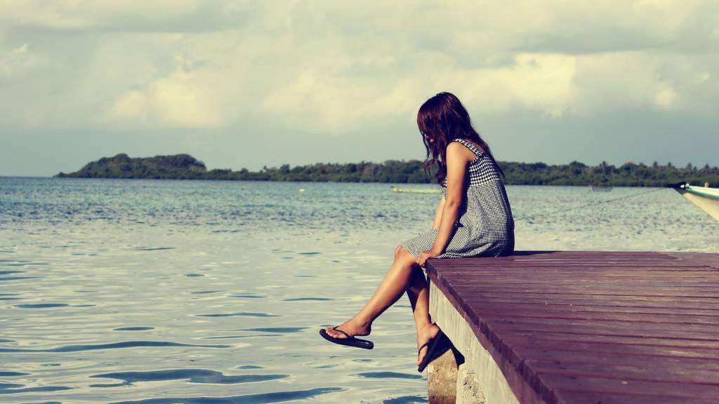mólón ülő nő vízparton