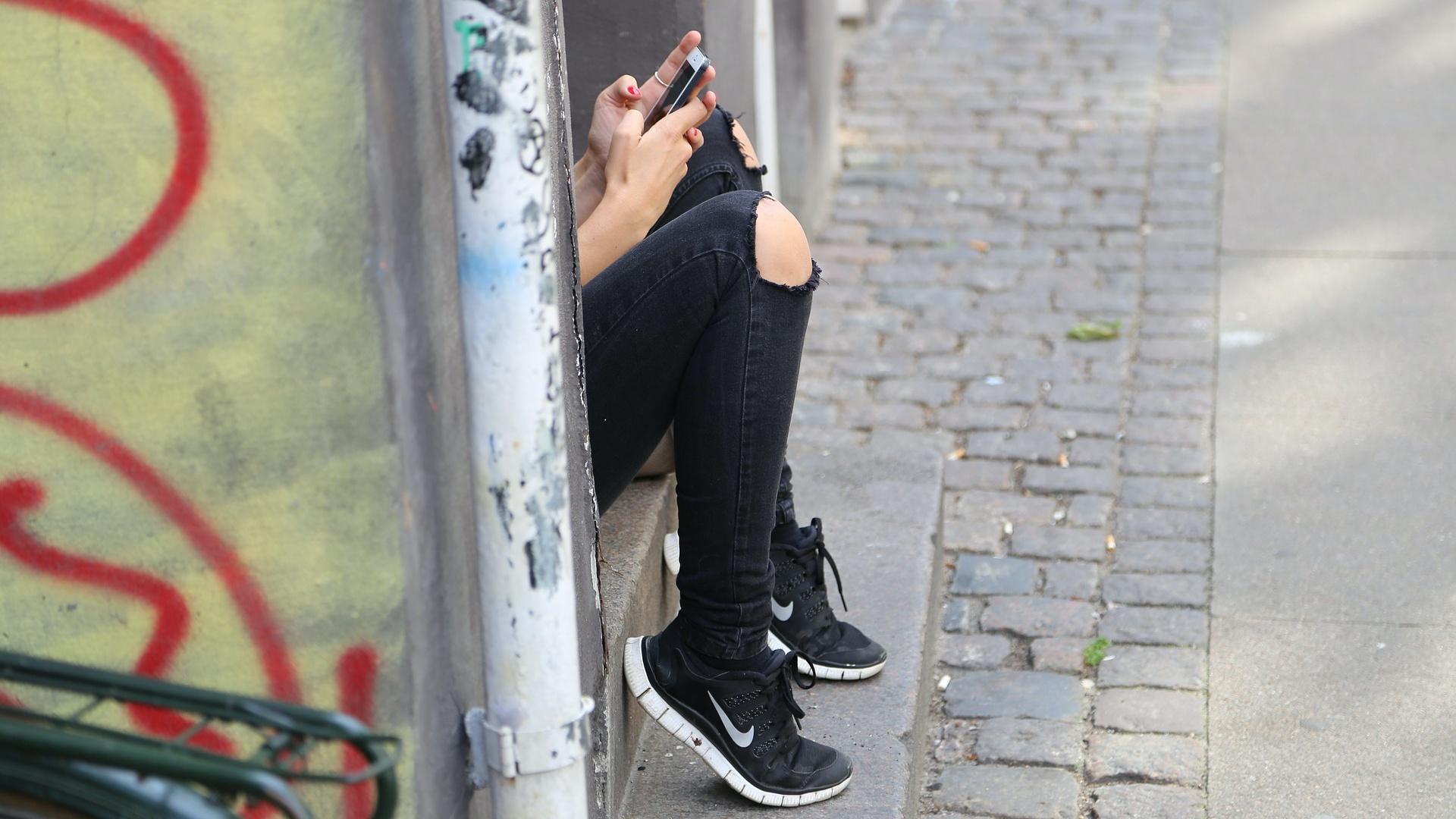 Tinédzser lány telefonozik az utcán