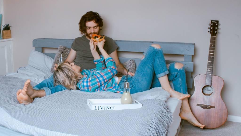 szerelmespár pizzát eszik az ágyban gitár mellett