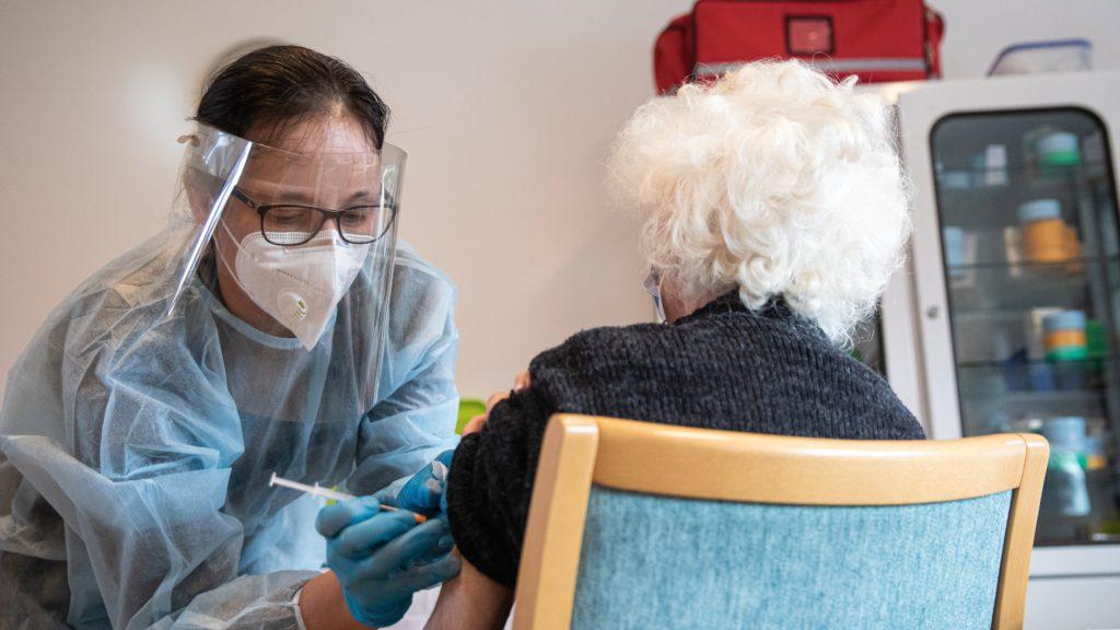 Egészségügyi dolgozó egy lakót olt be a Pfizer-BioNTech koronavírus elleni vakcinájának első adagjával a fővárosi Kálvin János Református Idősek Otthonában 2021. január 31-én.