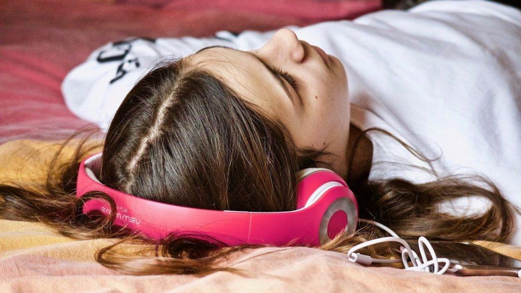 Kamaszlány zenét hallgat.