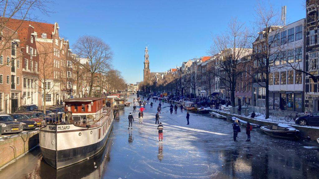 Korcsolyázók a befagyott Prinsengracht csatornán Amszterdamban 2021. február 13-án.