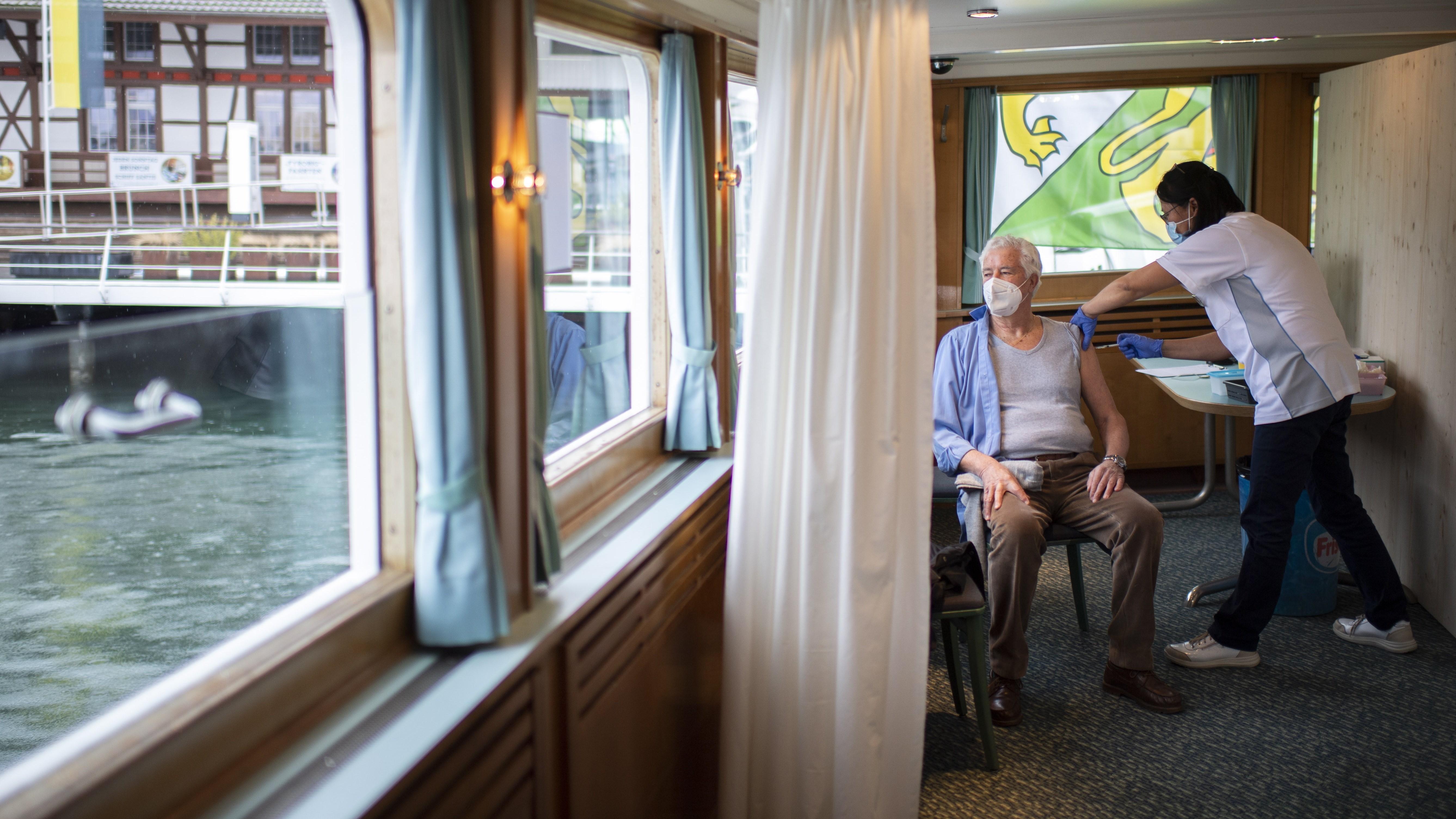 A 82 éves Valerio Amatit beoltják az új koronavírus ellen a Boden-tavon közlekedő MS Thurgau hajón Romanshornban 2021. február 2-án. Ezen a napon kezdte meg működését mozgó oltóközpontként a hajó, amelynek fedélzetén naponta akár 170 embert is beolthatnak az új koronavírus ellen három part menti svájci településen, Kreuzlingenben, Romanshornban és Arbonban.