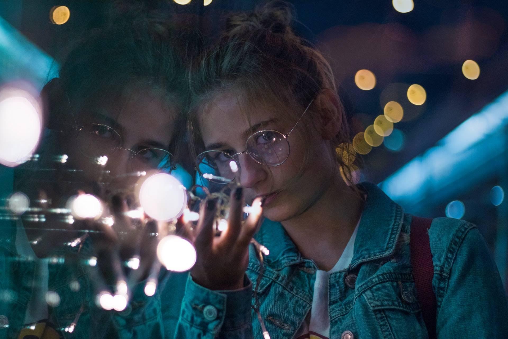 szemüveges nő ablaknál izzósorral