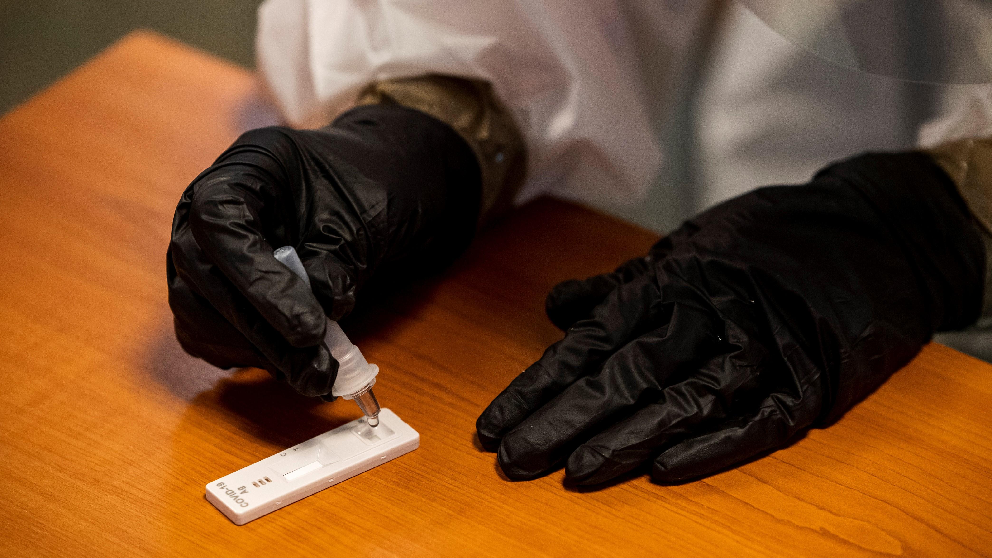 Mintát cseppent egy antigén koronavírus gyorsteszt paneljére egy, a köznevelésben dolgozók koronavírus-tesztelését végző orvostanhallgató a Budapest Főváros Kormányhivatala Egészségbiztosítási Főosztályának ügyfélszolgálatán 2021. január 2-án.