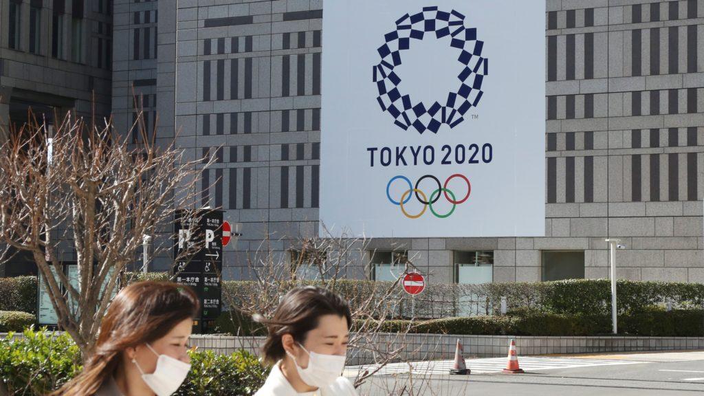 Két védőmaszkos nő megy a tokiói nyári olimpiát hirdető plakát előtt a japán fővárosban 2021. február 17-én. A koronavírus-járvány miatt 2020-ról 2021-re halasztott ötkarikás játékokat a tervek szerint 2021. július 23. és augusztus 8. között rendezik meg, de a legfrissebb közvéleménykutatások szerint a lakosság 80 százaléka vagy tovább halasztaná vagy meg sem rendezné az olimpiát.