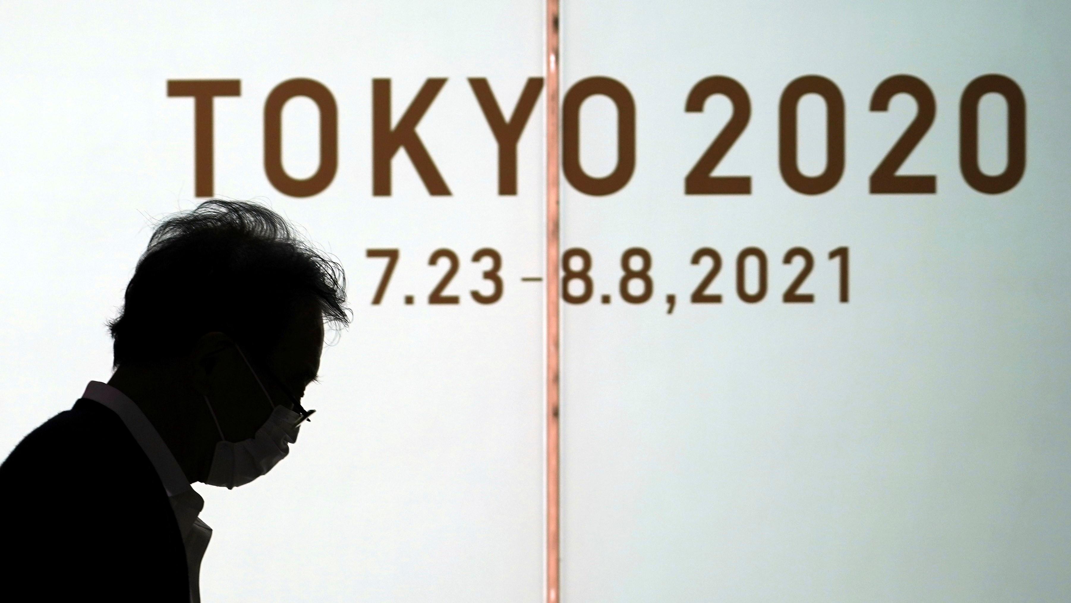 Védőmaszkos férfi megy a tokiói nyári olimpiát hirdető plakát előtt a japán fővárosban