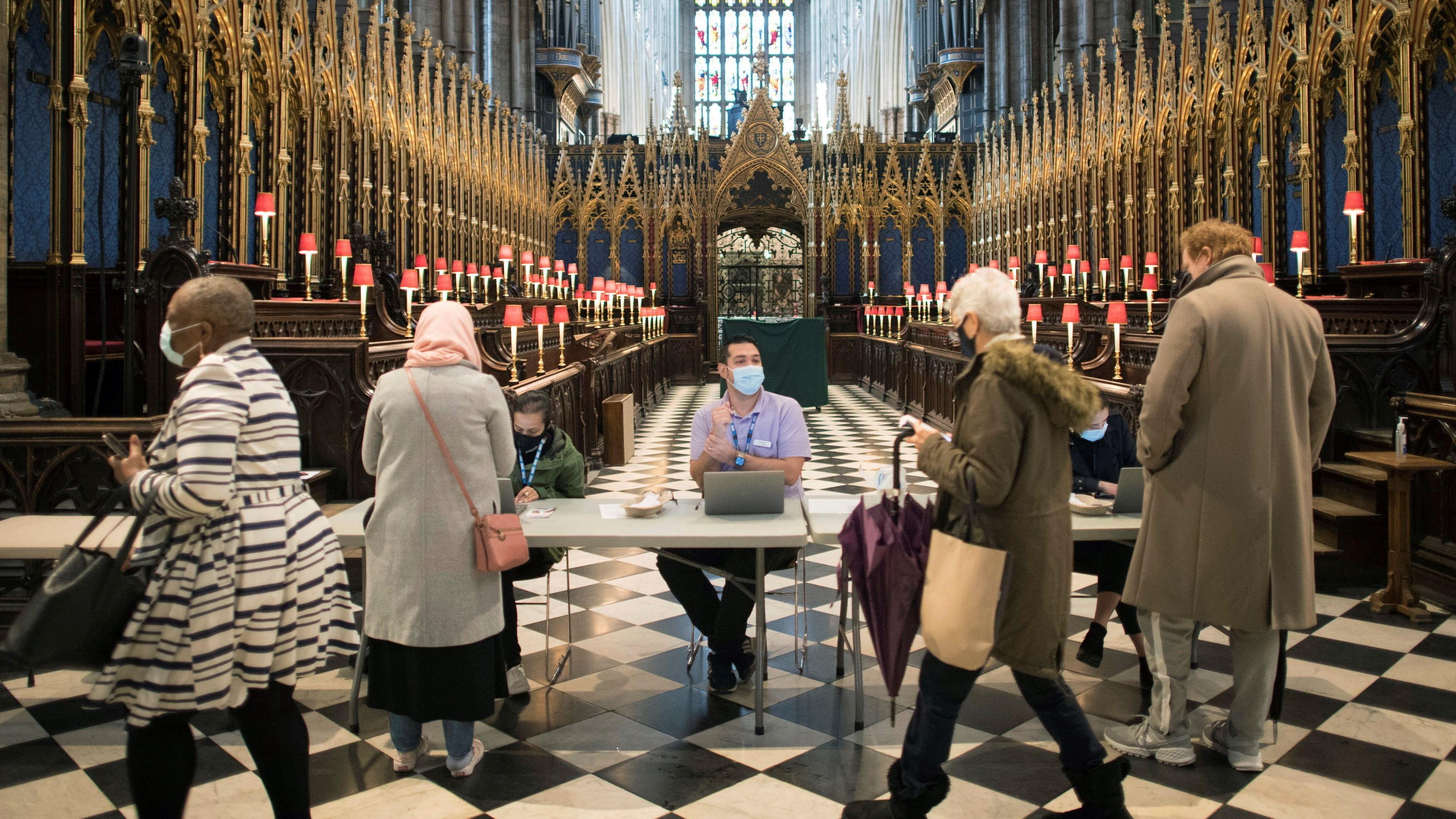 Emberek érkeznek a koronavírus elleni oltás felvételére a londoni Westminster-apátságban kialakított oltóközpontban 2021. március 10-én.