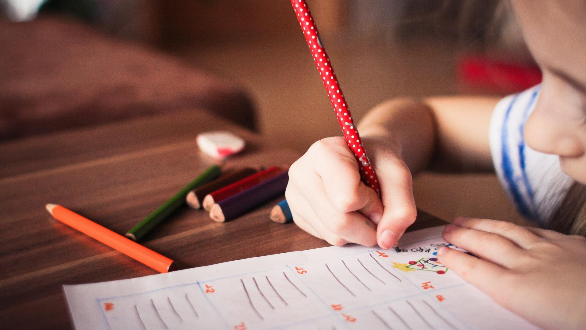 Kislány ír és rajzol egy füzetbe