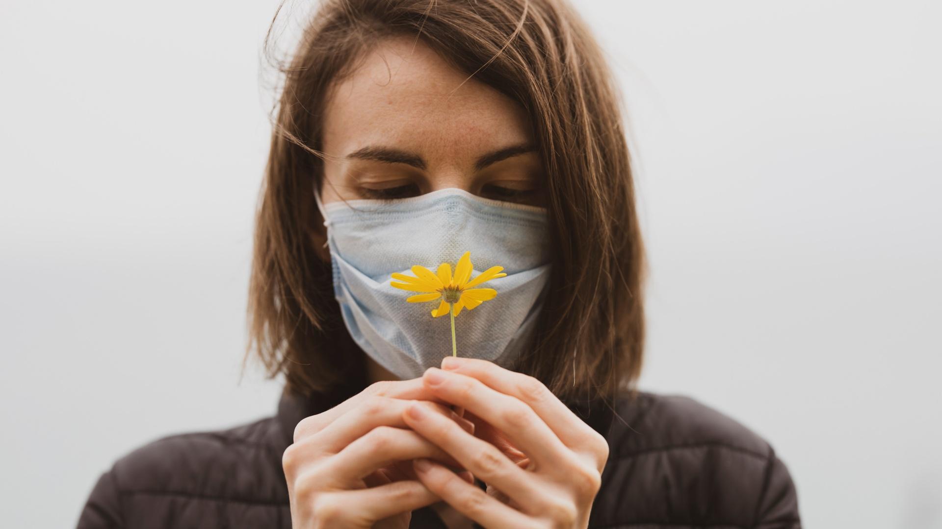Maszkos nő virágot tart az arca előtt